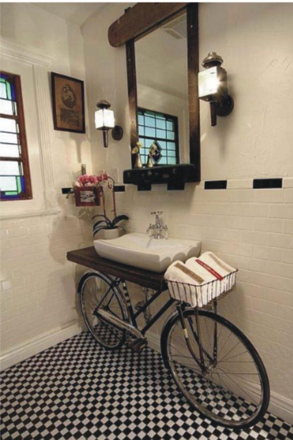 An old bicycle used as bathroom furniture